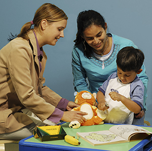 Healthcare provider and woman watching child play with medical toys.